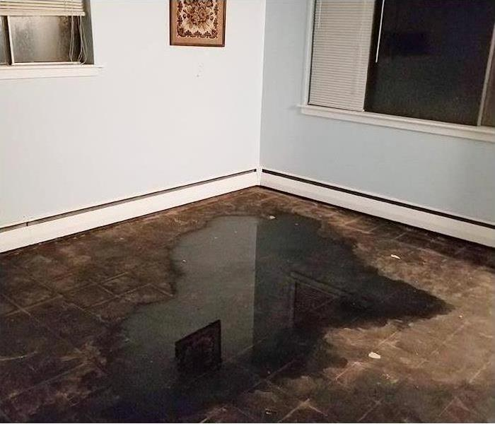 Soaked floor and walls after storm flooding and water damage
