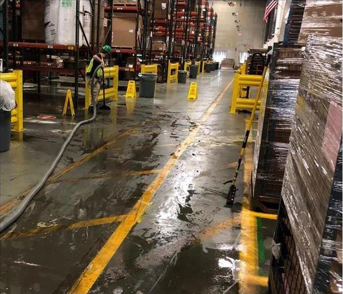 Soaked commercial warehouse from flooding, SERVPRO working cleaning