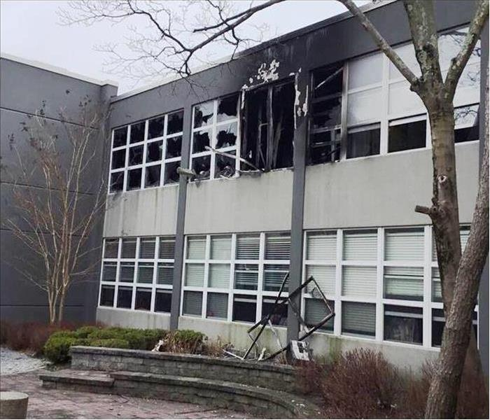 External photo of school with fire damages including black soot and broken windows
